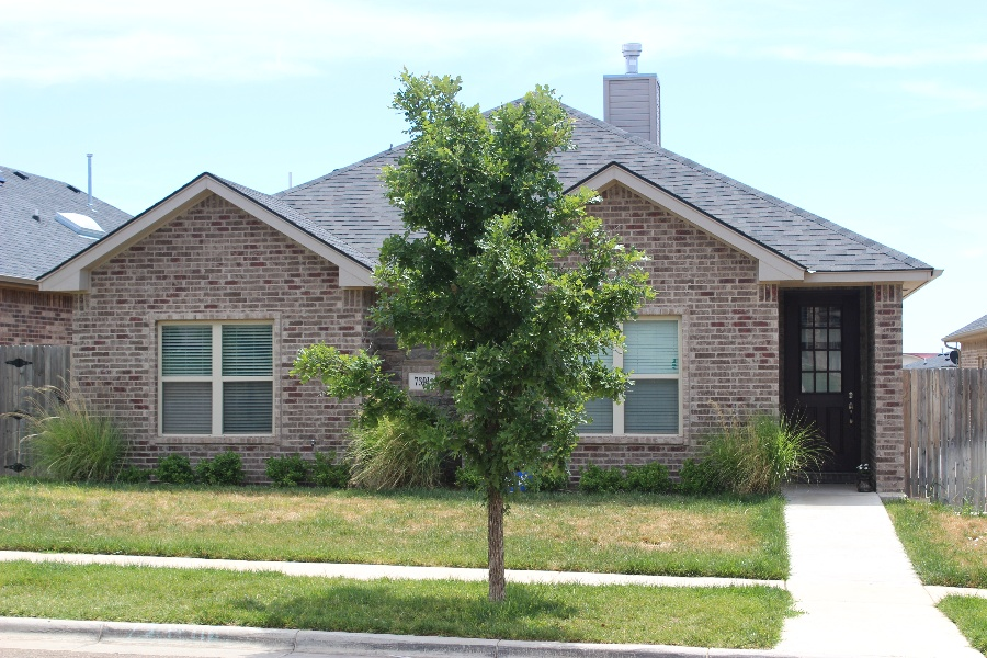 brown bricked home with small tree in front in the front yard